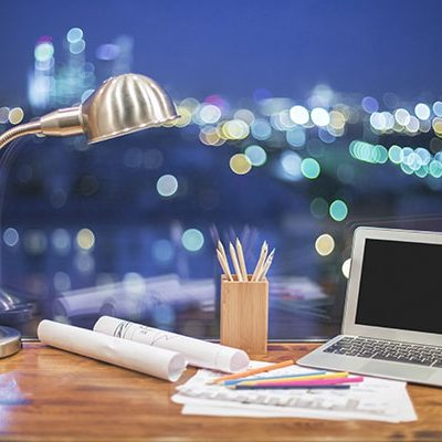 Front view of creative designer desktop with blank laptop, stationery items and table lamp on blurry night city background. Mock up